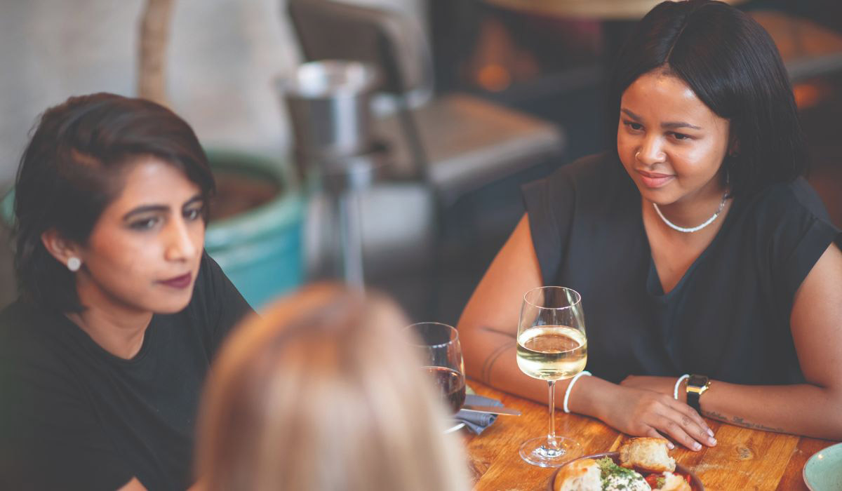 female-friends-dinning-having-wine-at-restaurant-the-square