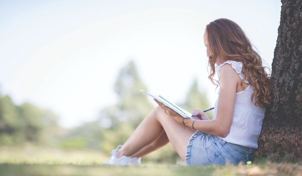 young-female-writing-in-the-park-the-estate